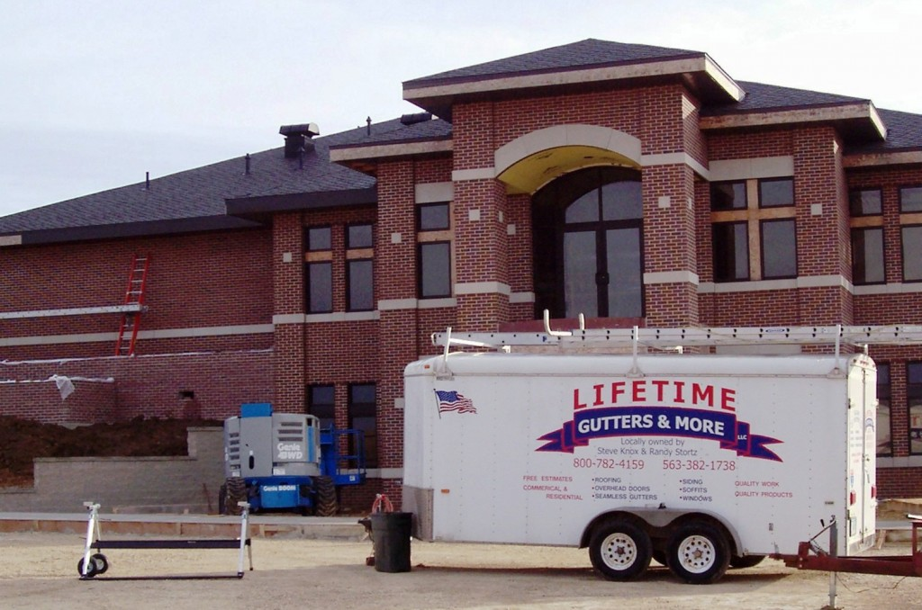 Lifetime Gutters trailer outside commercial building project.